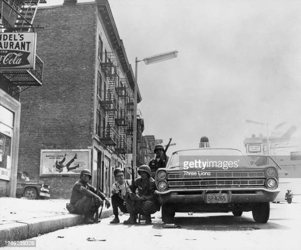 Troops and a newsman with a camera use a police car as cover from sniper fire during the riots in Newark, New Jersey, July 1967. The Newark riot...