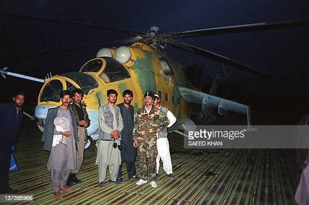 Troops belonging to strict Moslem Taliban militia pose on October 10 1996 in front of a Sovietmade MI24 helicopter gunship after an evening patrol...