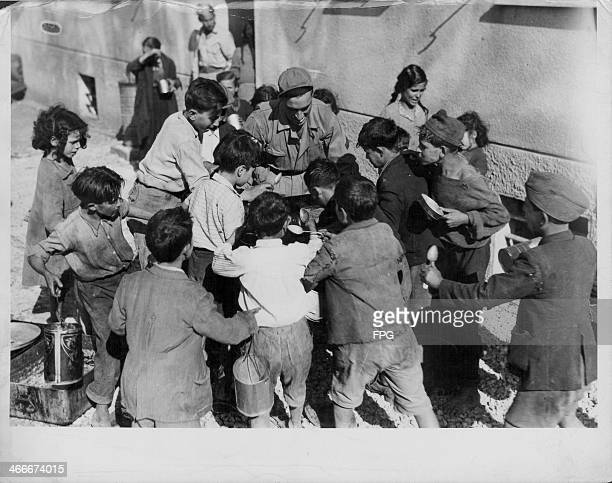 Troops feeding the starving children of Italy with any sare rations during World War Two, Italy, circa 1943-1945.