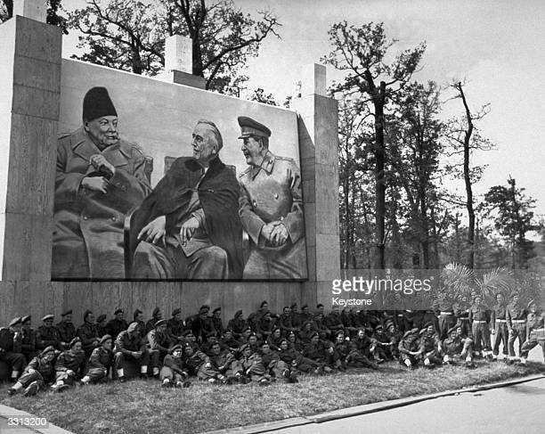 Troops from the British Victory Parade in Berlin rest under the picture of the 'Big Three' Churchill Roosevelt and Stalin