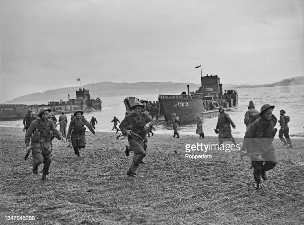 Troops from The Royal Air Force Regiment rush ashore on a beach from their LCT Mk5 landing craft as they rehearse invasion tactics in conjunction...