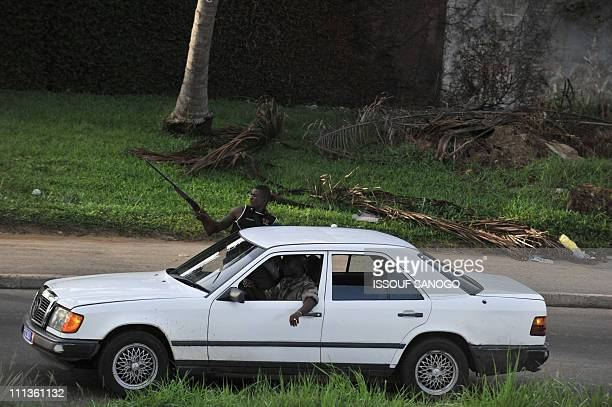 Troops loyal to Alassane Ouattara drive a vehicle along a street in Abidjan on April 1 2011 Ivory Coast strongman Laurent Gbagbo's forces repulsed an...
