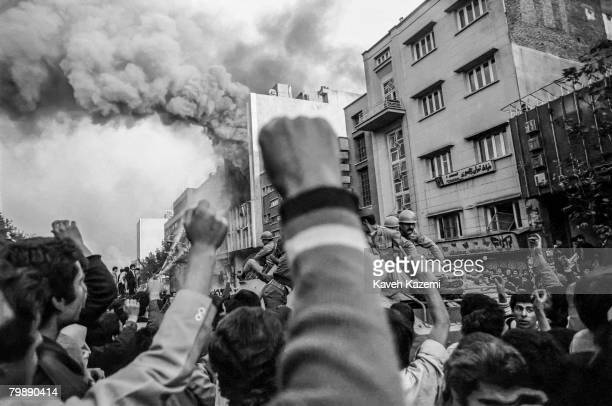 Troops loyal to Shah Mohammad Reza Pahlavi arrive to control a crowd of demonstrators outside a burning government building at the height of Islamic...