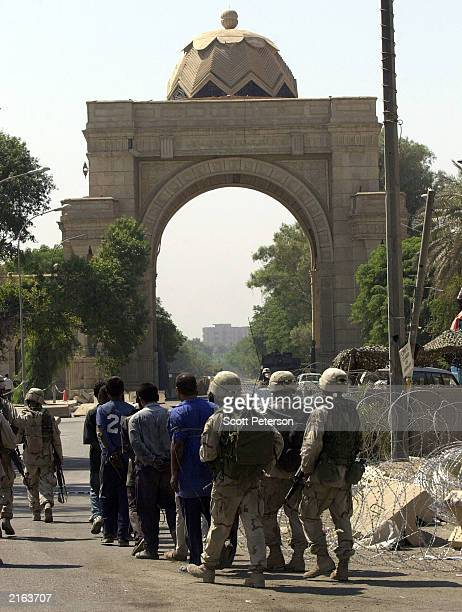 Troops march captured looters to the Baghdad presidential palace for detention July 9, 2003 in Iraq. U.S. Forces occupying Iraq have come under...