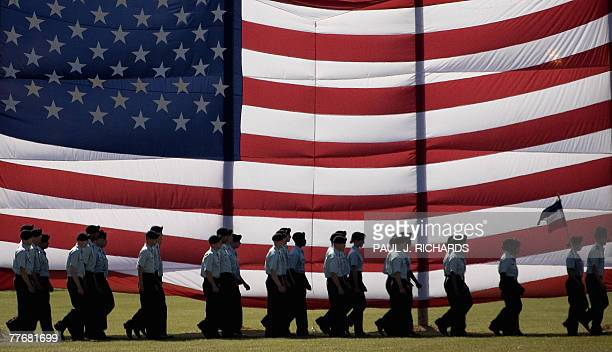 Troops march past a large American flag as they graduate from Basic Combat Training at Fort Jackson South Carolina 02 November 2007 AFP PHOTO/Jim...