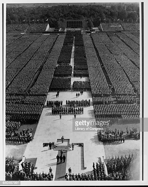 Troops mass in the huge Luitpoldhain Arena in Nuremberg. Adolph Hitler speaks from the podium. | Location: Luitpoldhain Arena, Nuremberg, Germany.