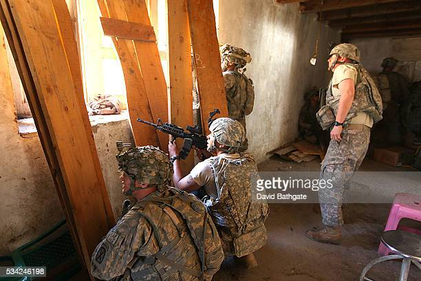 Troops of Charlie Company the US Army's 10th Mountain Division return fire on Taliban mountain side positions from the District Center building at...