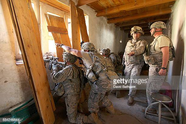Troops of Charlie Company US Army 10th Mountain Division return fire on mountainside Taliban positions from the District Center building at Barge...