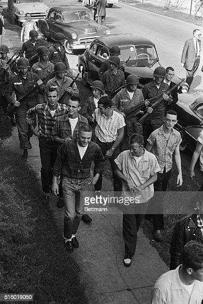 Troops of the 101 Airborne escort teenage white student away from Little Rock Central High School who part of a group which tried to stage a walkout...