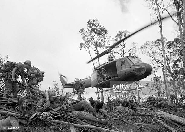 Troops of the 101st Airborne Division rush to take positions after jumping off a helicopter in a landing zone northwest of Dak To