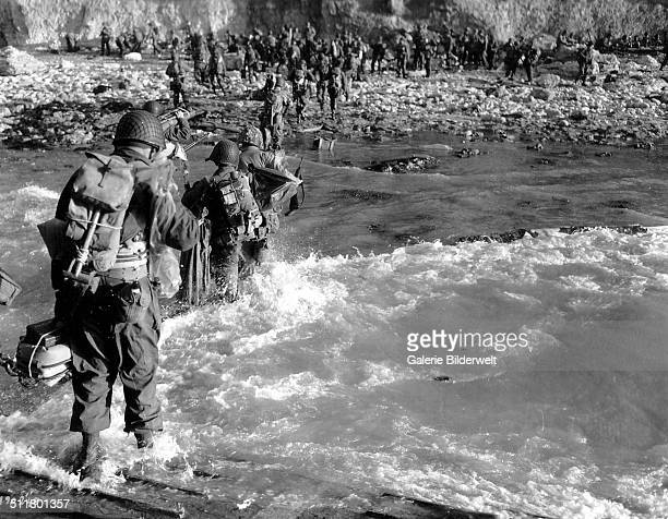 Troops of the 5th Engineer Special Brigade wade through the surf at at Fox Green Omaha Beach 8th June 1944 They are part of the invasion forces...
