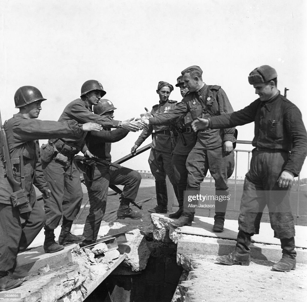 US troops of the 69th Infantry Division (left), shake hands with Russian troops in a staged photo on the wrecked bridge over the Elbe at Torgau, Germany, to mark the previous day's link-up between American and Soviet forces, 26th April 1945. Among the Americans are Bernard E. Kirschenbaum and Richard Johnson (second and third from left, respectively). The Soviet soldier in the centre is Lt. Charles Thau, a Pole drafted into the Soviet Army in 1943.