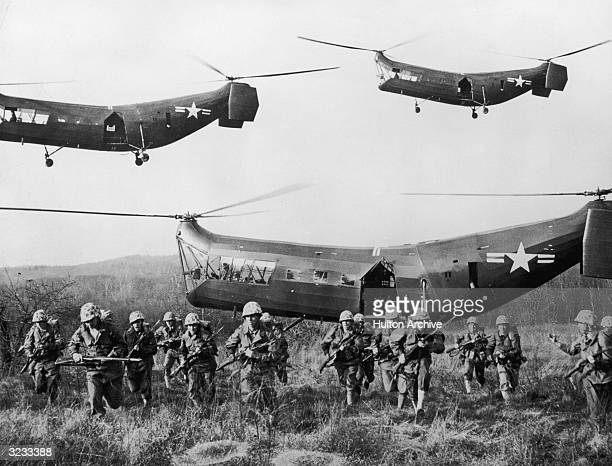 Troops of the United States Marine Corps disembarking from Piasecki HRP-1 'Rescuer' tandem-rotor helicopters during an experiment in vertical assault...