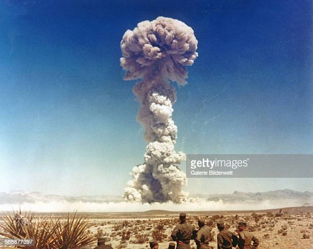 Troops of the US Army 11th Airborne Division watch a plume of radioactive smoke rise after a blast at Yucca Flats during Operation Buster Jangle Dog...