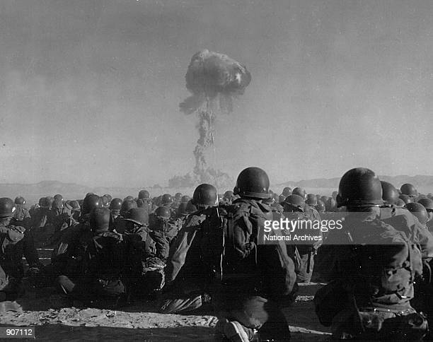 Troops of the U.S. Army 11th Airborne Division watch a plume of radioactive smoke rise November 1, 1951 after a blast at Yucca Flats, Nevada .