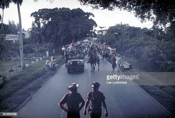 Troops of victorious ProCastro calvary led by Camilo Cienfuegos seen from distance entering city on day of huge celebration