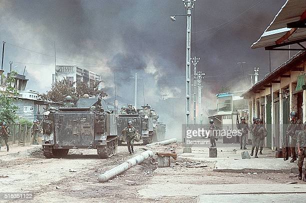 Troops on foot and in personnel carriers trek along a street in northern Saigon which is engulfed in smoke from fierce fighting during the Tet...