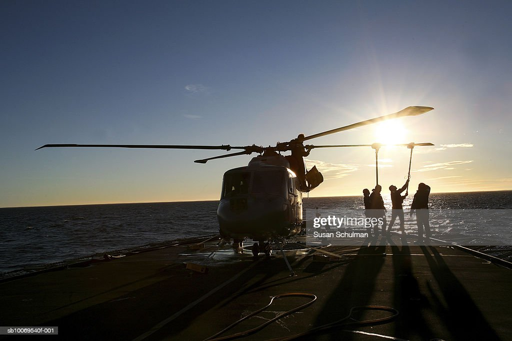 Silhouette of people cleaning helicopter at dusk : News Photo