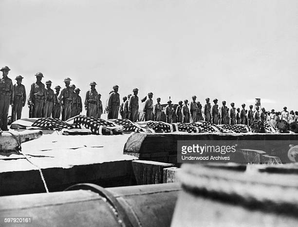 US troops stand at attention behind the flag draped coffins of their countrymen killed in the battle of Midway Midway Island June 1942