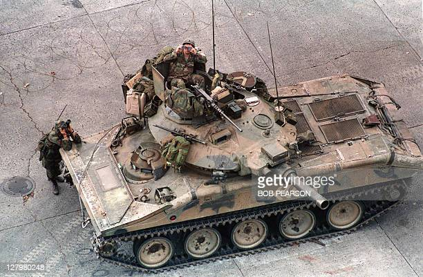 Troops survey the buildings surrounding the Vatican embassy in Panama City during Operation Just Cause, on December 28, 1989 as forces remain...