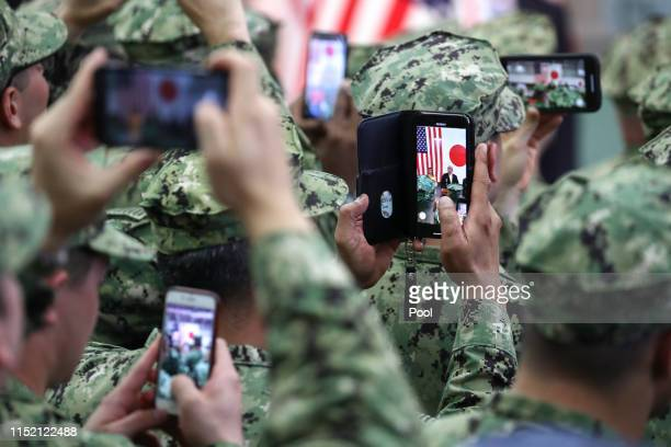 Troops take pictures of U.S. President Donald Trump and First Lady Melania Trump as they aboard Japan Maritime Self-Defense Force's helicopter...