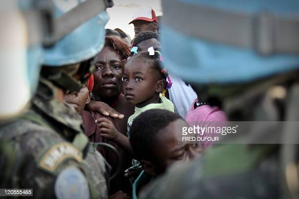 Troops try to contol Haitians queuing for aid at an old military airfield in Port-au-Prince on January 23, 2010. UN troops fired warning shots and...