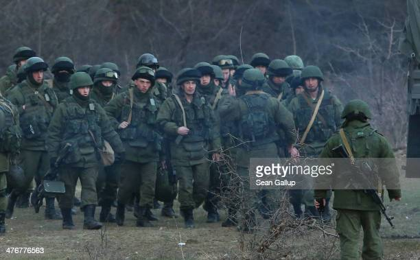 Troops under Russian command assemble before getting into trucks near the Ukrainian military base they are blockading on March 5 2014 in Perevalne...