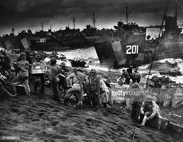 Troops unload invasion supplies from Coast Guard and Navy landing craft on the black sand coast of Iwo Jima, a few hours after U.S. Marines had...