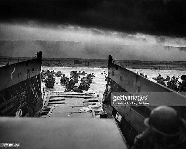 Troops wading through water after reaching Normandy and landing Omaha beach on D Day, 1944.