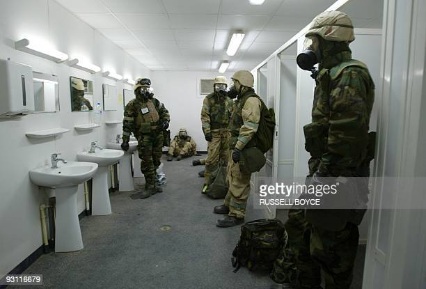 US troops wait in the toilets and shower rooms wearing protective suits during an air raid warning in Kuwait 21 March 2003 Men showering scrambled to...