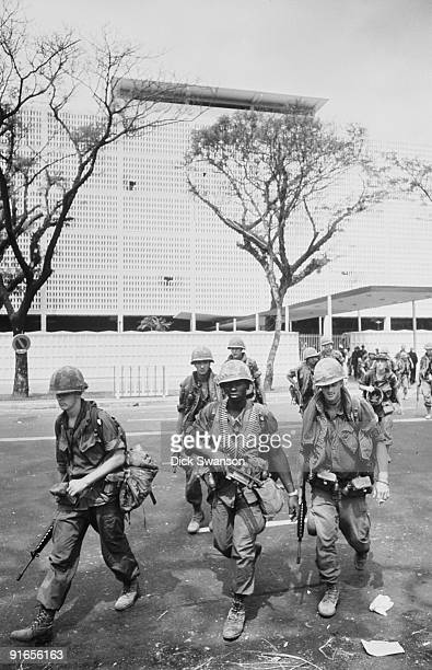 US troops walk across the grounds of rthe US Embassy in the aftermath of an attack on the compound during the Tet Offensive Saigon Vietnam early 1968
