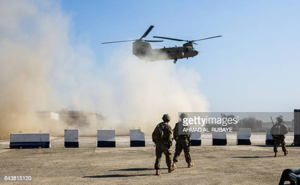 US troops walk as a US Army C47 Chinook helicopter flies over the village of Oreij south of Mosul on February 22 where a temporary military base has...
