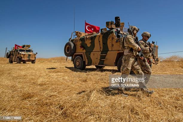 TOPSHOT US troops walk past a Turkish military vehicle during a joint patrol with Turkish troops in the Syrian village of alHashisha on the outskirts...