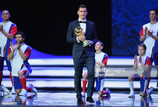 Trophy bearer Miroslav Klose walks onto stage with the trophy during the Final Draw for the 2018 FIFA World Cup Russia at the State Kremlin Palace on...