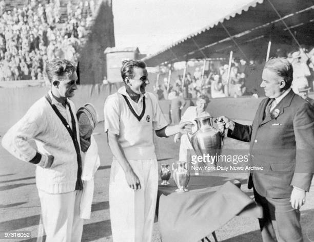Trophy is presented to Fred Perry by Holcombe Ward after he won the National Singles Tennis Championship Looking on is Jack Crawford