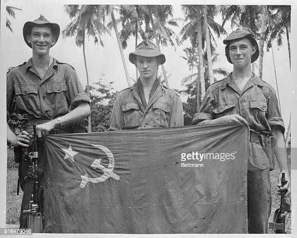 Trophy of their action in the Malaya jungle, a banner carried by the Red guerilla troops, is exhibited by three British soldiers who captured the...