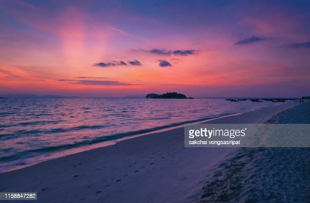 tropical beach against dramatic sky during sunrise at koh lipe island in thailand - インド洋 ストックフォトと画像