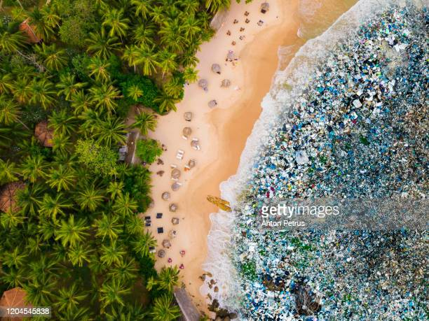 tropical beach and trash in the water. ocean pollution concept with plastic and garbage - ゴミ捨て場 ストックフォトと画像