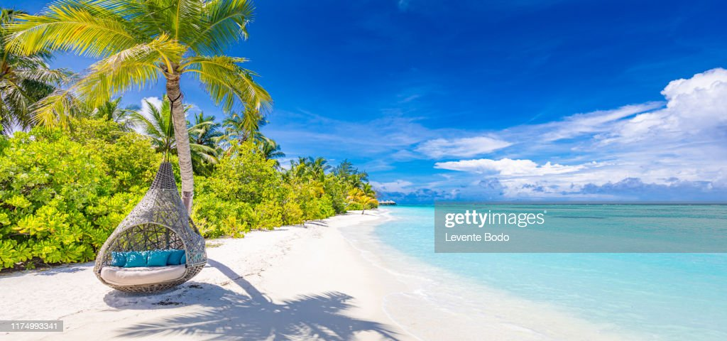Tropical beach background as summer landscape with beach swing or hammock and white sand and calm sea for beach banner. Perfect beach scene vacation and summer holiday concept. Boost up color process : Stock-Foto