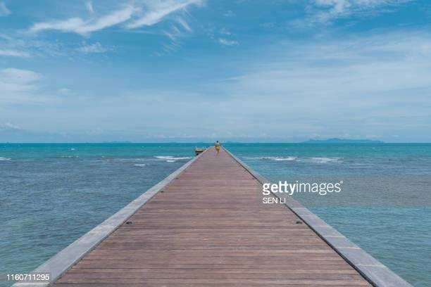 tropical beach seascape with sunlight and blue sky, a wood bridge in front on sea with young lady walking on it, ko samui, thailand - convés - fotografias e filmes do acervo