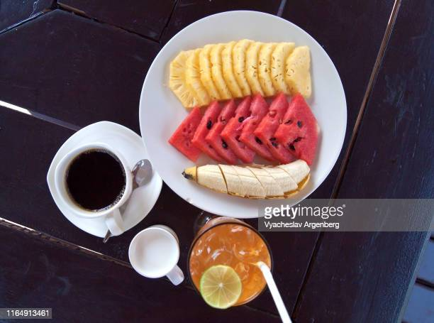 tropical breakfast: slices of fresh watermelon, banana and pineapple, coffee and juice - argenberg stock pictures, royalty-free photos & images