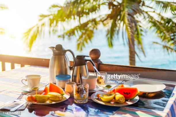 Tropical breakfast with fresh fruit, tea and curd on the background of palm trees and the ocean