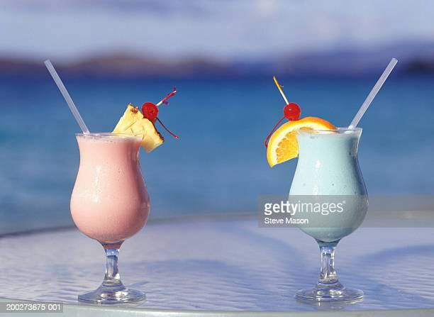 Tropical drinks standing on tray by sea, close-up, surface view