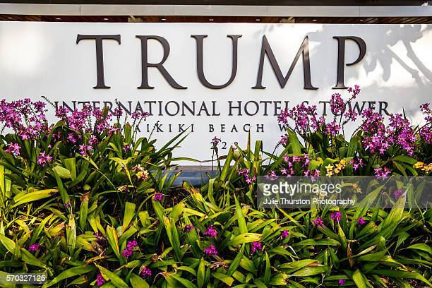 Tropical flowers and front entrance sign of Trump International Hotel Waikiki Beach Five Star luxury hotel residences owned by Donald Trump wealthy...