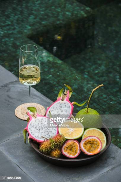 tropical fruit and champagne by the pool - champagne colored stock pictures, royalty-free photos & images