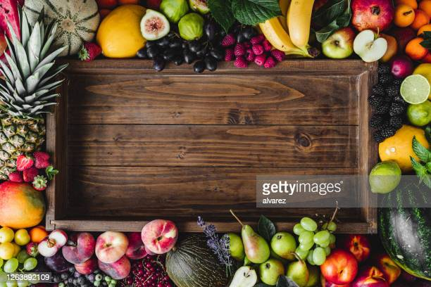 tropical fruits around empty wooden box - tropical fruit stock pictures, royalty-free photos & images