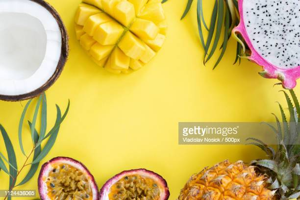 tropical fruits mango, pitayam coconut and passion fruit on yellow background - パッションフルーツ ストックフォトと画像