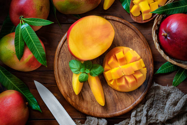 tropical fruits: sliced mangos in a wooden plate on a table in rustic kitchen - mango stock pictures, royalty-free photos & images