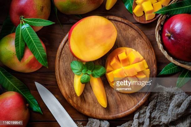 tropische früchte: geschnittene mangos in einer holzplatte auf einem tisch in rustikaler küche - mango stock-fotos und bilder