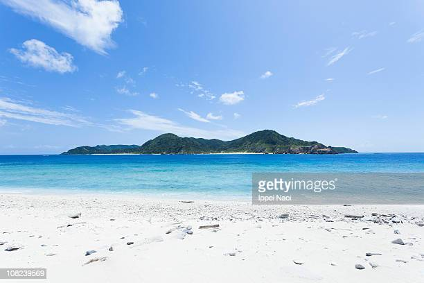 tropical island on horizon over clear coral water - ippei naoi stock photos and pictures
